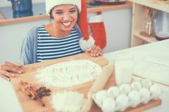 Jeune femme heureuse souriant ayant l'amusement avec des préparations de Noël utilisant le chapeau de Santa Images stock