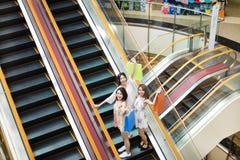 Jeune femme heureuse sur l'escalator dans le centre commercial Photo stock