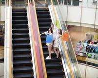 Jeune femme heureuse sur l'escalator dans le centre commercial Image stock