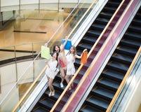 Jeune femme heureuse sur l'escalator dans le centre commercial Photographie stock