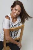Jeune femme heureuse sur la chaise Photographie stock