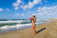 Jeune femme heureuse sur une plage floue au crépuscule Images stock