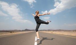 Jeune femme heureuse sur une route vide dans le désert de l'Oman Photographie stock libre de droits