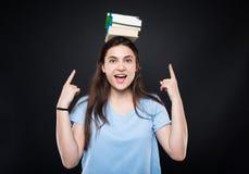 Jeune femme heureuse tenant des livres sur sa tête photos libres de droits