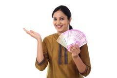 Jeune femme heureuse tenant des notes de l'Indien 2000 Photographie stock libre de droits