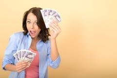 Jeune femme heureuse tenant l'argent semblant heureux et ravi images stock