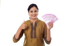 Jeune femme heureuse tenant l'Indien 2000 notes de roupie et faisant thu Images stock