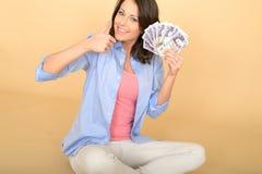 Jeune femme heureuse tenant la fan de l'argent Photographie stock