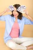 Jeune femme heureuse tenant la fan de l'argent se reposant sur le plancher Photos stock