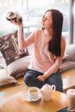 Jeune femme heureuse tenant la haute son furet d'animal familier en café Photos libres de droits