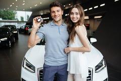 Jeune femme heureuse tenant la voiture proche avec l'ami Image libre de droits