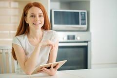 Jeune femme heureuse tenant le comprimé et regardant l'appareil-photo photos stock
