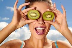 Jeune femme heureuse tenant le kiwi Photo stock