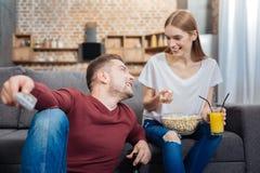 Jeune femme heureuse tenant le maïs éclaté et regardant son ami Image libre de droits