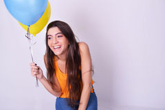 Jeune femme heureuse tenant les ballons colorés Photographie stock libre de droits