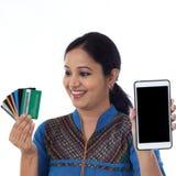 Jeune femme heureuse tenant les cartes et le téléphone portable de débit Image stock