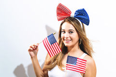 Jeune femme heureuse tenant les drapeaux américains Photo stock