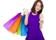 Jeune femme heureuse tenant les paniers et le téléphone portable Images libres de droits