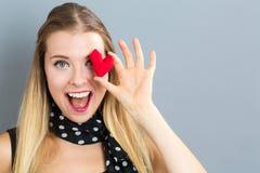 Jeune femme heureuse tenant un coussin de coeur Photos libres de droits