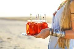 Jeune femme heureuse tenant un plat avec boissons à la partie d'été image libre de droits