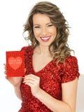Jeune femme heureuse tenant une carte de valentines Photographie stock