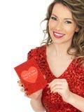Jeune femme heureuse tenant une carte de valentines Photo stock