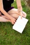 Jeune femme heureuse tout en affichant un livre Photos libres de droits