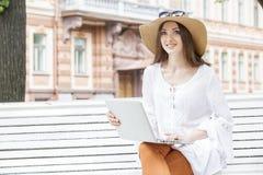 Jeune femme heureuse travaillant avec un ordinateur portable se reposant sur un banc photos stock