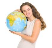 Jeune femme heureuse étreignant le globe Photographie stock