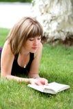 Jeune femme heureux affichant un livre Images stock