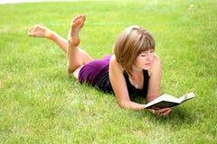 Jeune femme heureux affichant un livre Image libre de droits