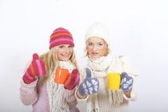 Jeune femme heureux de l'hiver deux avec la cuvette de thé Photos stock