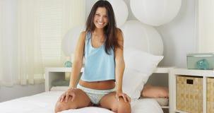 Jeune femme hispanique s'asseyant sur rire de lit photos libres de droits