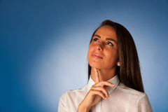 Jeune femme hispanique songeuse pensant devant le backgroun bleu Image libre de droits