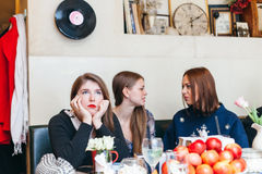 Jeune femme ignorée par ses amis dans le cafétéria Photo libre de droits