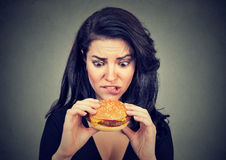 Jeune femme implorant un hamburger savoureux image libre de droits