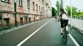 Jeune femme inconnue avec le backsack montant sa bicyclette le long de chemin urbain de vélo banque de vidéos