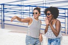 Jeune femme indiquant à quelque chose son ami étonné Image libre de droits