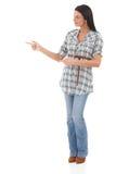 Jeune femme indiquant et regardant la droite Photographie stock