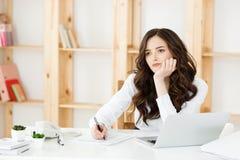 Jeune femme inquiétée d'affaires travaillant avec le document au bureau moderne images libres de droits