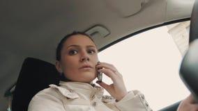 Jeune femme inquiétée parlant au téléphone portable se reposant dans la voiture banque de vidéos