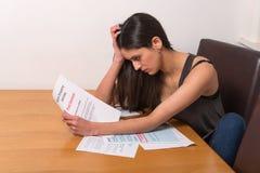 Jeune femme inquiétée au-dessus des factures Photos libres de droits