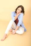 Jeune femme insouciante décontractée s'asseyant sur le plancher avec le verre du vin et de la cigarette Images stock