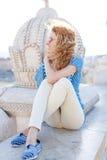 Jeune femme insouciante s'asseyant au monument Image stock