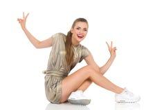 Jeune femme insouciante s'asseyant sur un plancher Photo stock