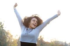 Jeune femme insouciante souriant avec des bras augmentés Photo stock