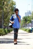 Jeune femme intégrale descendant la rue avec le téléphone portable Image libre de droits