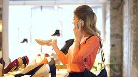 Jeune femme invitant le smartphone au shoestore banque de vidéos
