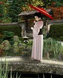 Jeune femme japonaise dans le kimono rose avec le parasol se tenant dans un jardin Image stock