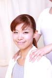 Jeune femme japonaise obtenant un massage  d'épaule Photos stock